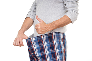 man pulling the waistband of his pants outwards with one hand and giving thumbs up with other