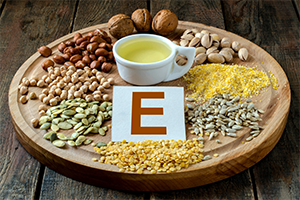 foods with vitamin E such as nuts and seeds on a round wooden tray