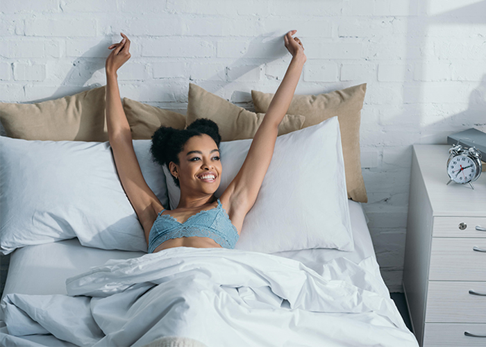 young african american woman waking up in a bright room