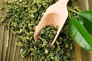 dried green tea leaves with a wooden scoop