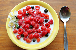 top down view of a breakfast bowl full of fresh berries in yoghurt