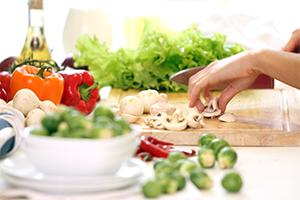 woman chopping fresh vegetables in the kitchen