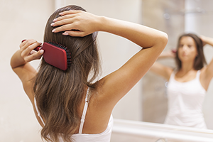 woman brushing her healthy head of hair