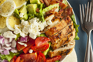 close up of a healthy hearty cobb salad with eggs, cheese, greens, tomatoes, onions, and chicken