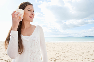 a young woman at the beach holding a conch shell up next to her ear
