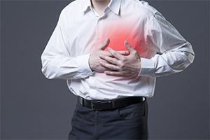 man having a heart attack, clutching his chest