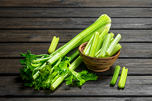 chopped celery stalks in a small wooden bowl next to a large bunch of celery