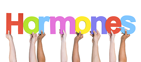 "different pairs of hands holding up colourful letters to spell ""Hormones"""