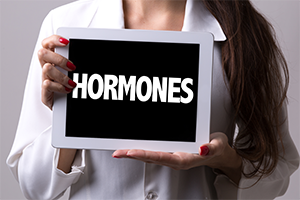 female doctor holding up a sign saying hormones