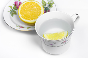teacup with water inside and a wedge of lemon