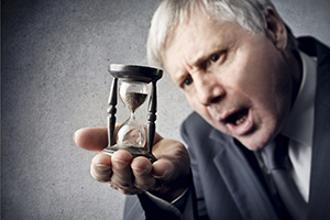 aged man holding an hourglass