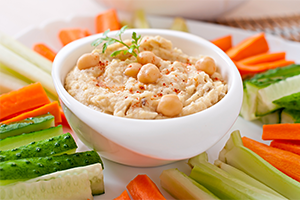 hummus in a dip bowl with carrot and celery sticks neatly arranged on the plate below it