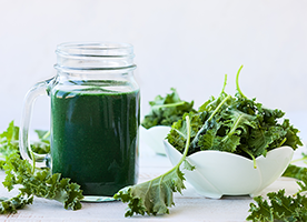 kale smoothie in a mason jar with a bowl of kale and scattered kale leaves on a white table