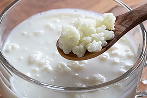 wooden spoon scooping kefir out from a glass