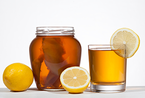 large jar of kombucha with a glass of kombucha garnished with lemon slice