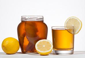 large jar of kombucha with a glass of kombucha garnished with lemon slice