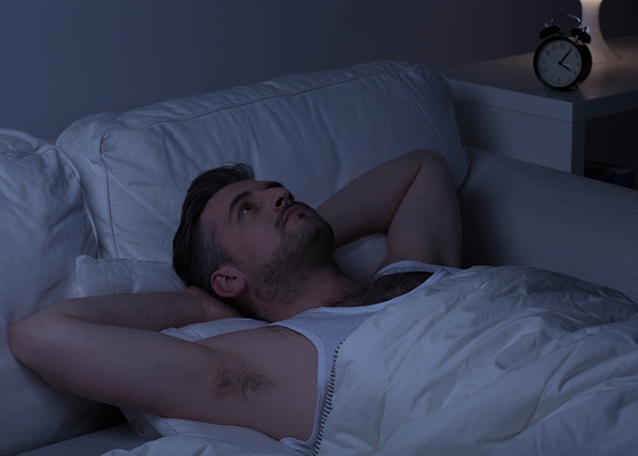 man awake in bed at night suffering from lack of sleep