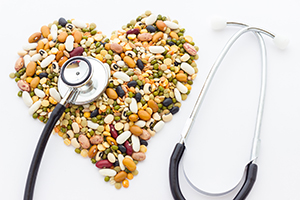Doctor's stethoscope and a pile of legumes shaped as a heart