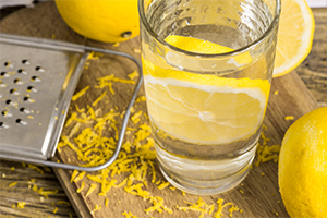 glass of water with lemon inside on a wooden board with other lemons around and a grater