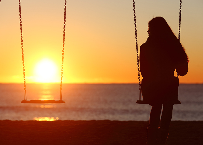 woman alone on a swing on the beach at sunset