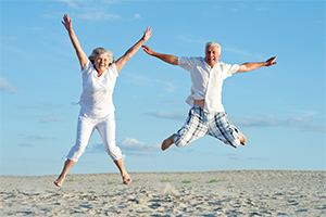 an elderly couple at the beach jumping with arms and legs stretched out