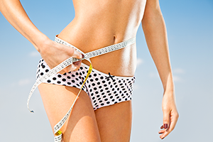 thin fit woman in underwear bottom holding a measuring tape around her thin waist