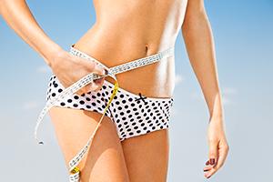thin fit woman in underwear bottom holding a measuring tape around her thin waist