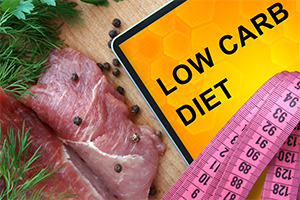 lean meat next to a pink measuring tape and a sign that says low carb diet