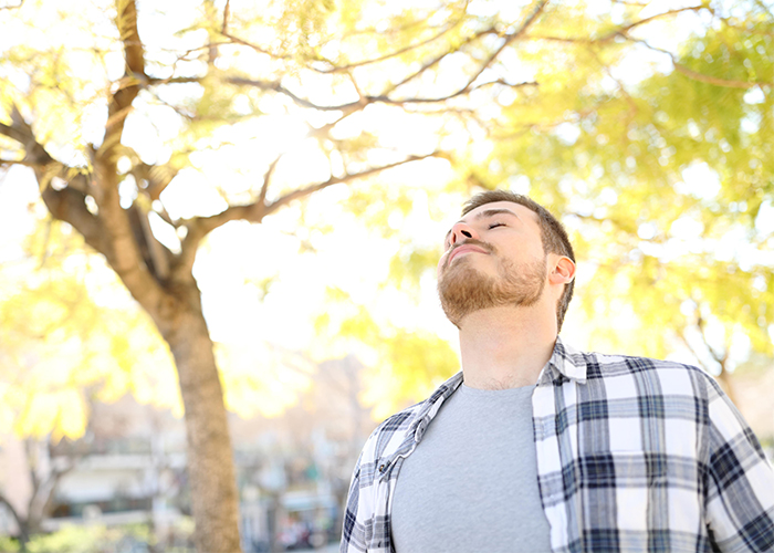man taking a deep breath of fresh air outside