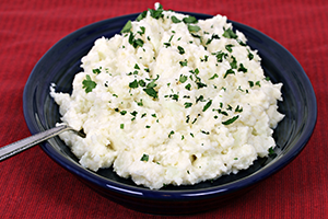 mashed cauliflower on a dark blue plate topped with parsley
