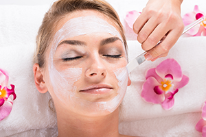 woman lying on a spa bed having a facial peel applied