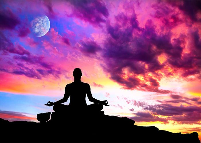 man meditating cross legged under a sunset sky