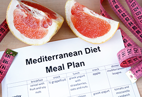 Sheet of paper with Mediterranean Diet Meal Plan information, with wedges of grapefruit and a pink measuring tape around it