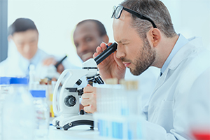 scientist looking down a microscope doing micronutrient testing