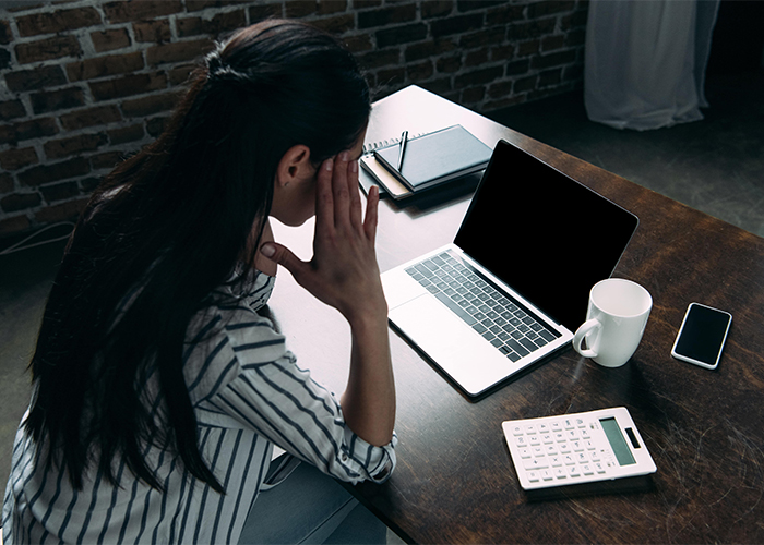 woman with headache working at her desk