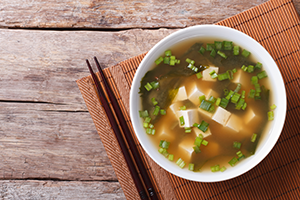 top down view of a bowl of miso soup with seaweed, tofu, and spring onions, on a wooden table mat and chopsticks