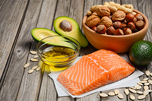 natural sources of trans fats such as salmon, avocado, olive oil and nuts on a wooden table