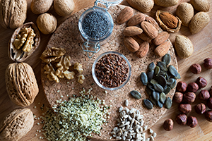 top down shot of different nuts and seeds on a wooden table