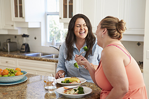 two women enjoying conversation over breakfast meals
