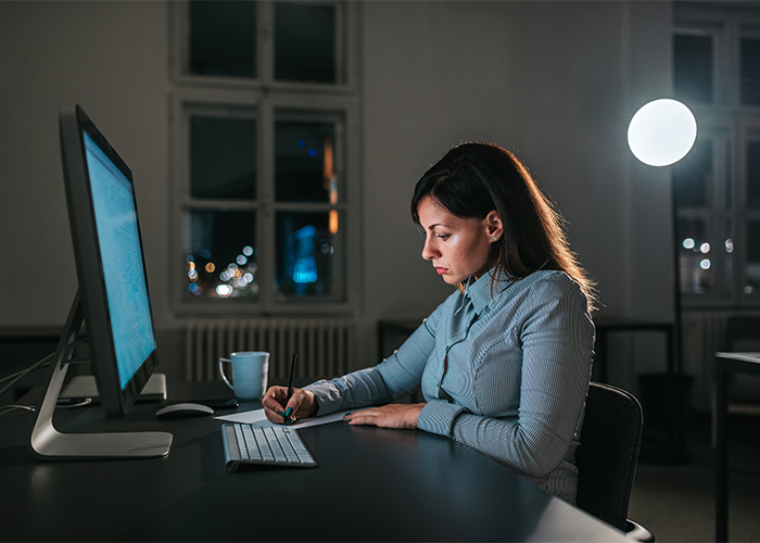 woman overworking at her desk late at night