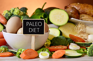 a small sign with the words paleo diet on it with different paleo foods in the background