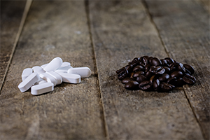 small piles of white pills next to a pile of coffee beans on a wooden table