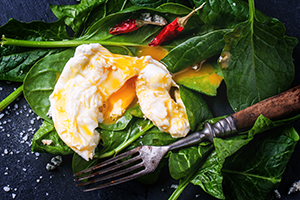 poached eggs sliced open on top of a bed of spinach