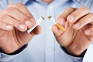 man's hands breaking a cigarette to quit smoking