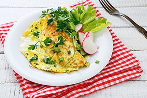egg omelette with fresh parsley and side salad on a red checkered tablecloth