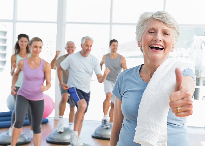 senior woman giving thumbs up with people exercising