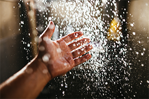 close up of a guy's hand under a shower with water pouring down