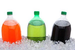 three different bottles of soda packed in ice