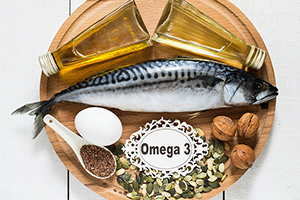 different omega 3 fatty acid food sources laid out on a round wooden base