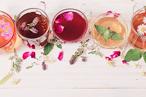 different glasses of colorful floral teas on a white wooden table
